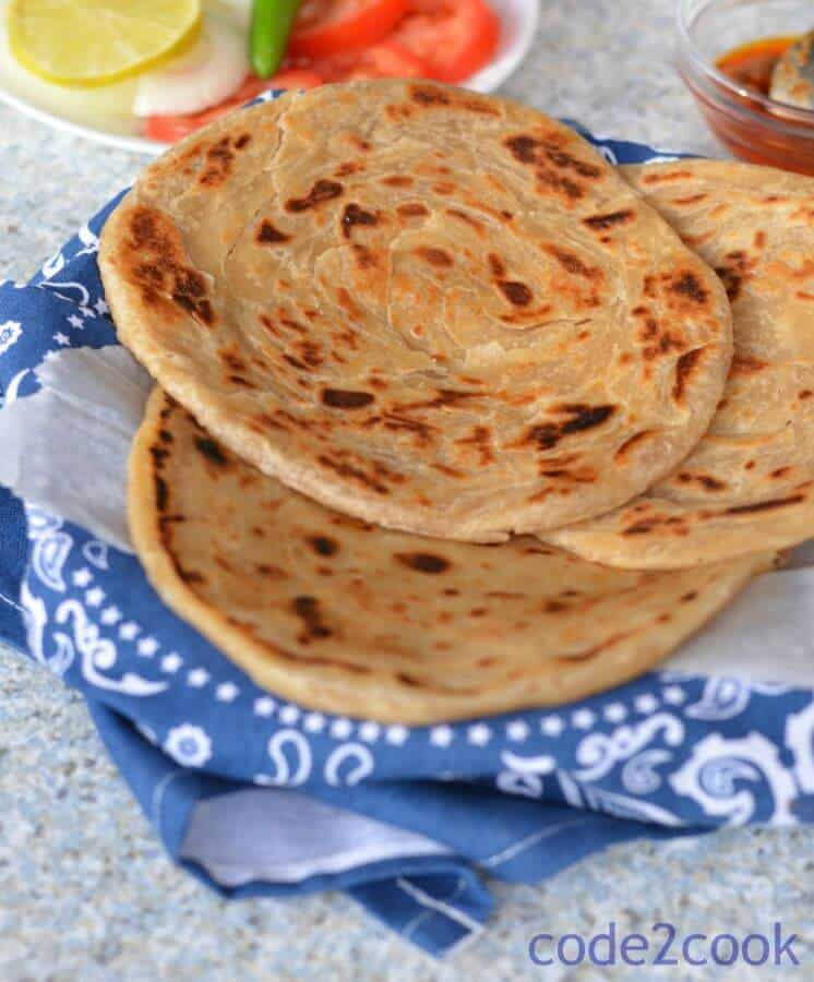 Kerala Parotta or Malabar parotta is a unique parotta dish from Malayali cuisine. It is a layered paratha or flaky paratha made with refined flour. Kerala parotta is a common street food in southern India. It is served with vegetable kurma or coconut stew.