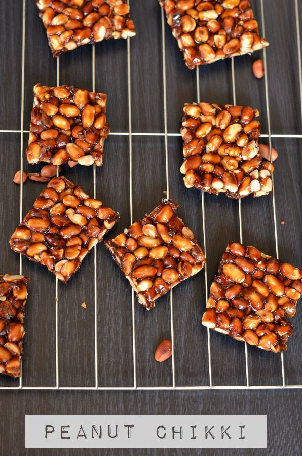 close up click for peanut chikki. Placed on rack and peanuts are scattered around.