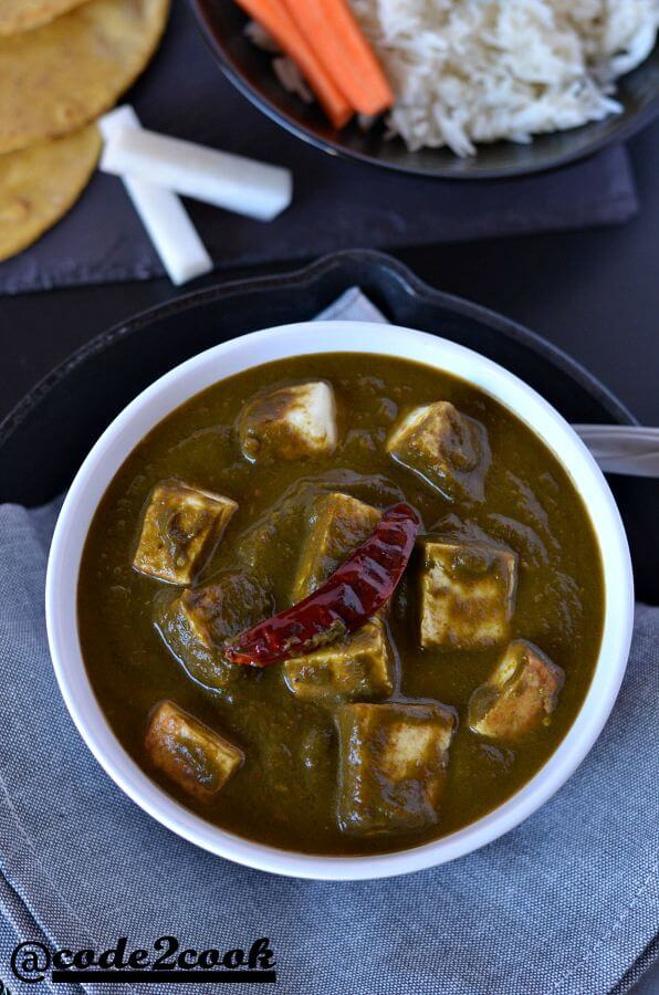 instant pot palak paneer is clicked from top served in white bowl and garnished with red chili