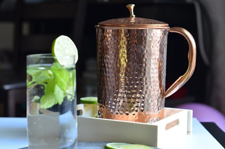 Copper pitcher is kept in a wooden tray. glass is filled with water with lemon wedges & mint leaves.
