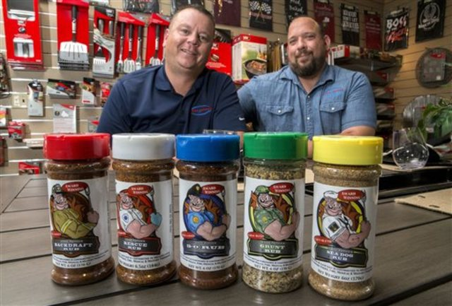In this June 15, 2015 photo, Chris Bohnemeir, left, and Mike Radosevich, founders of Code 3 Spices Inc., pose with a selection of their barbecue spices at Hearthside, a grill and fireplace store in Belleville, Ill., that sells their product. The founders have expanded their operations to 700 stores in 22 states and continue to donate a portion of their sales to first responders, Backstoppers, military organizations that assist veterans, Operation Homefront and Safe Call Now, a 24-hour suicide and crisis prevention hotline for first responders and military. (Derik Holtmann/Belleville News-Democrat via AP)