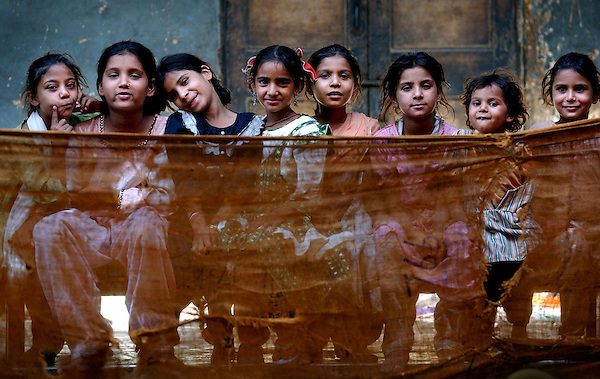 Muslim children sit inside Dariya Khan Ghhumnat Rahat refugee camp set up outside a school in the state of Gujarat in Ahmedabad, India May 10, 2002. The extent of the damage and displacement of more than 120,000 people has threatened the secular ideals of India and left the government under attack for its inadequate relief arrangements.