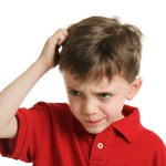 Child in red shirt scratching head while looking confused