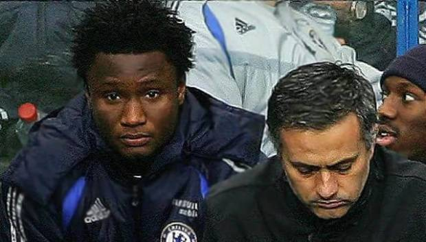 Mikel watches haplessly beside Jose Mourinho during a match.