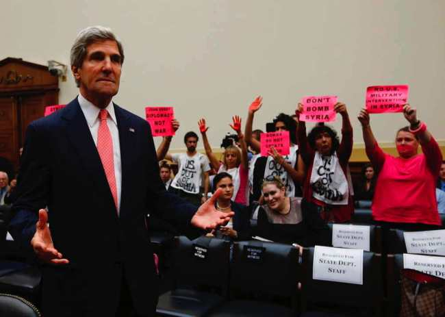 U.S. Secretary of State Kerry reacts as he waits for U.S. Secretary of Defense Hagel and General Dempsey to arrive at a U.S. House Foreign Affairs Committee hearing on Syria in Washington