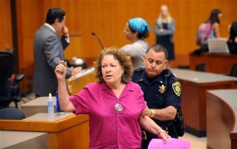 A police officer leads protester Cynthia Papermaster from a University of California, Berkeley classroom while Professor John Yoo, left, prepares to teach on Monday, Aug. 17, 2009, in Berkeley, Calif. Anti-war activists protested on the University of California, Berkeley campus Monday to call for the firing of a law professor who co-wrote legal memos that critics say were used to justify the torture of suspected terrorists. (AP Photo/Noah Berger)