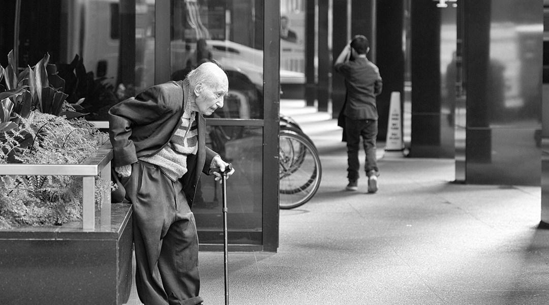 Un viejito caminando con dificultad por la calle