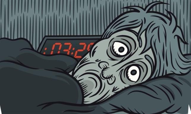 Hombre con insomnio y un reloj digital