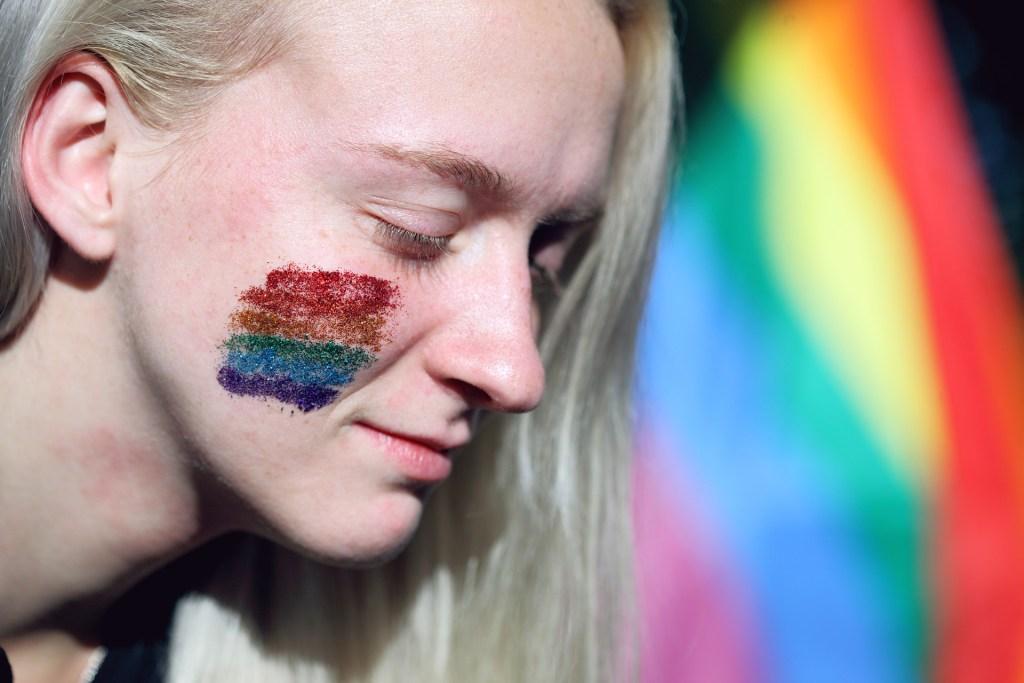 Mujer con los colores rojo, naranja, amarillo, verde, azul y morado pintados en la cara. De fondo hay una bandera del colectivo LGTB, con esos colores.