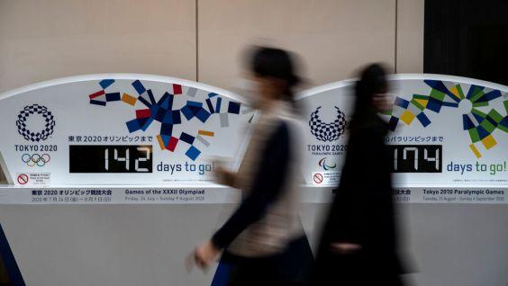 Gente con mascarilla pasando por la cuenta atrás para los JJOO de Tokyo 2020 / fuente: elespañol.es