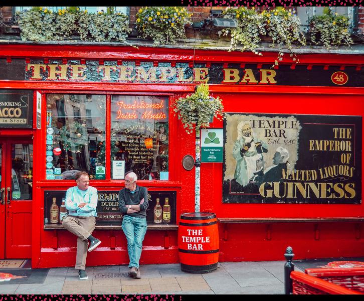 Deux hommes assis devant Temple Bar à Dublin
