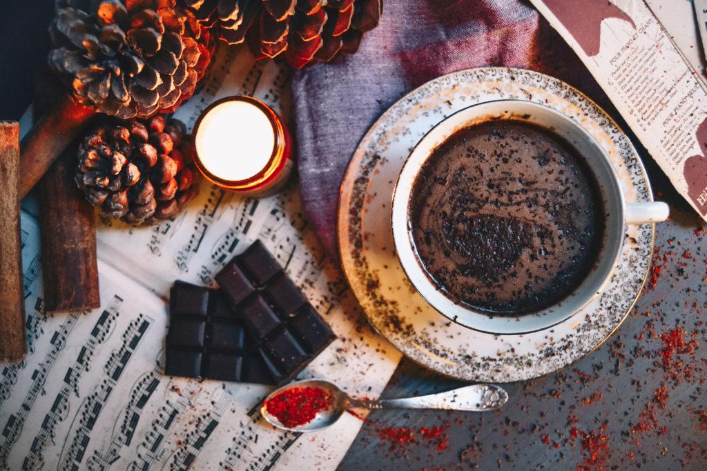 Un chocolat chaud épais, crémeux, bien chocolaté et légèrement pimenté. La boisson chaude est entourée d'une bougie, de pommes de pins, de piment, de notes musiques, de chocolat et de bâtons de cannelle.