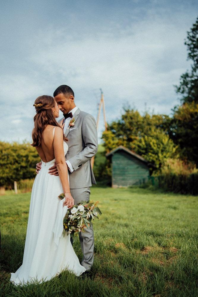 Brautpaar bei ihrem Paarshooting auf einer saftig-grünen Wiese.