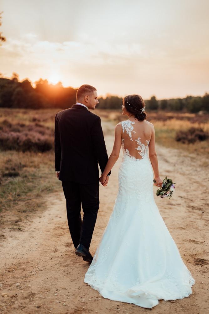 Brautpaar geht auf sandigem Boden Händchen haltend durch eine verträumte Heidelandschaft. Die Sonne geht gerade hinter den Bäumen unter.