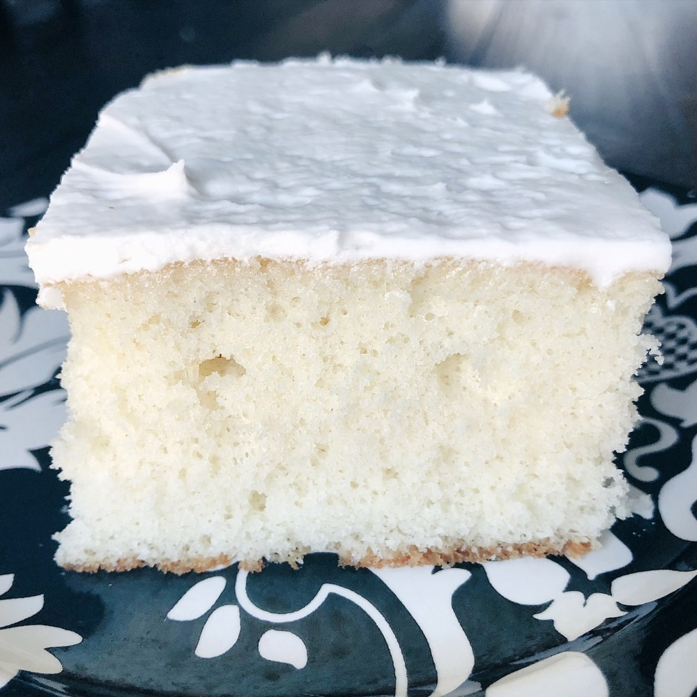 white cake with white frosting on black and white plate