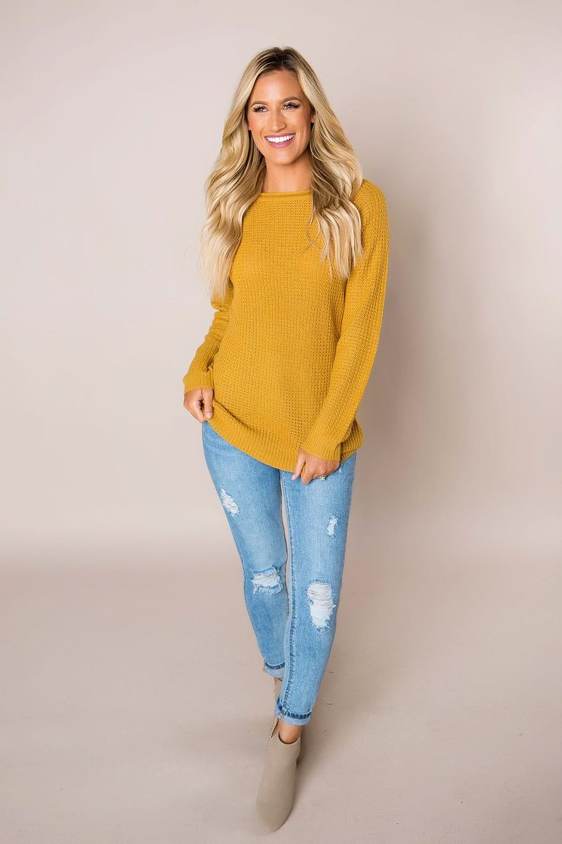 girl with yellow sweater and blue jeans ripped up from a boutique