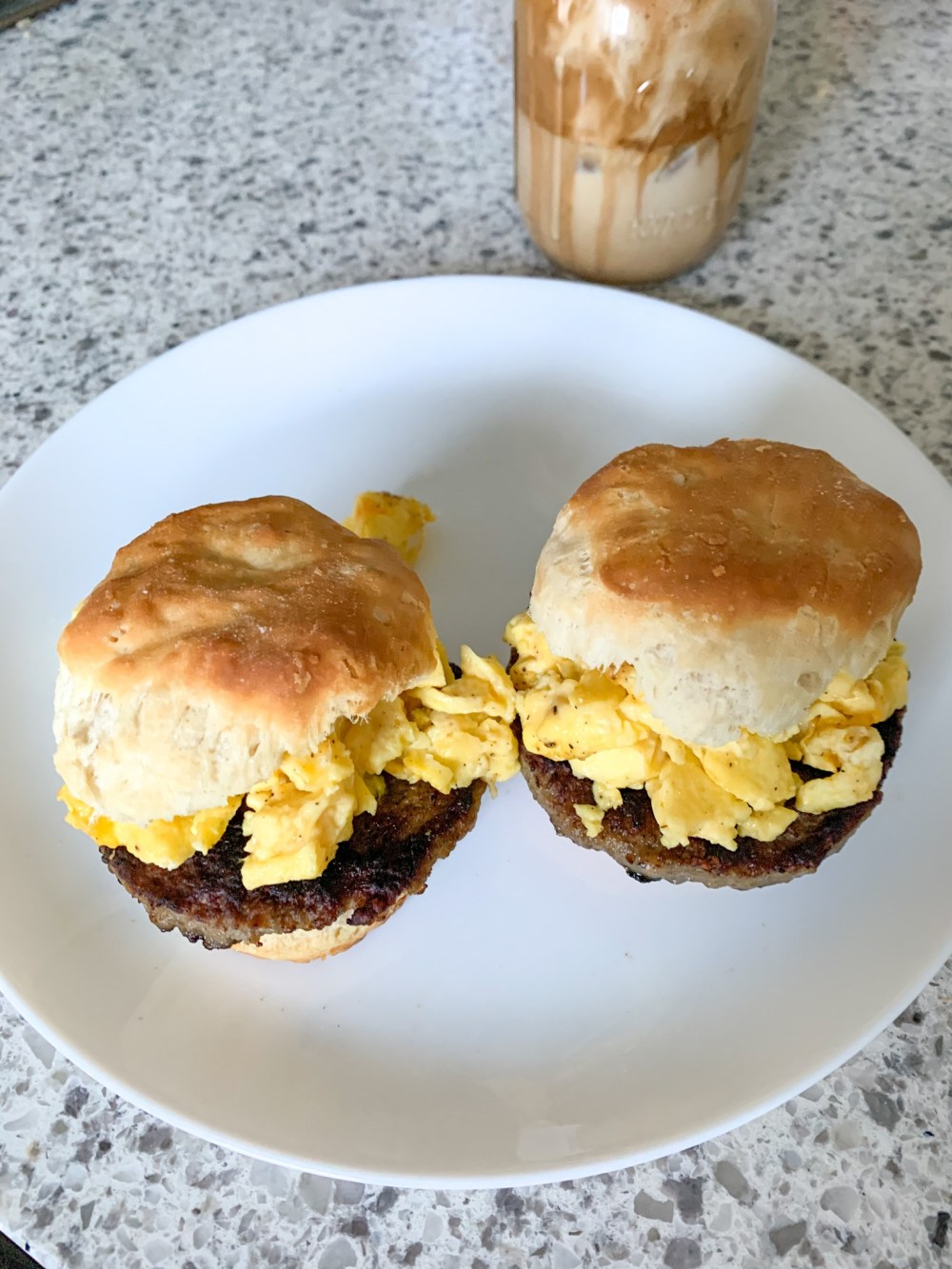 scrambled egg over sausage patty on biscuit