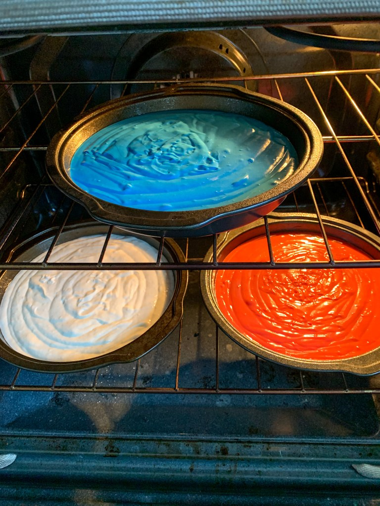 3 cake pans in oven one red, one white, one blue