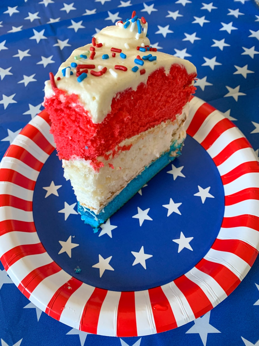 red. white, and blue cake with white icing and red, white, and blue sprinkles