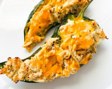 two halves of stuffed poblano peppers on white plate