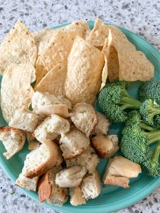 chips, cut up bread, and broccoli on teal plate