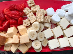 pieces of cheesecake, strawberries, rice krispy treats, pound cake, and marshmallows on a red plate
