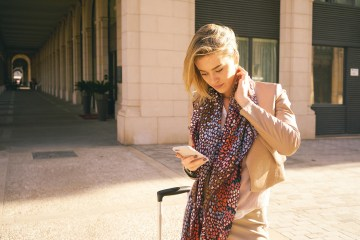young modern business woman arrived in a European city checking a mobile travel app.
