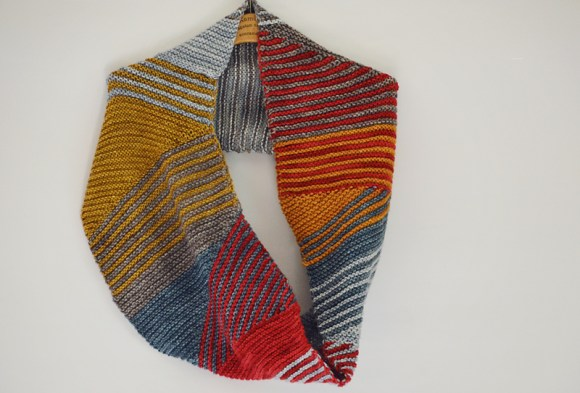 A photo showing the Simple Sprinkle snood pattern, knit in blue, yellow, orange and red tones.