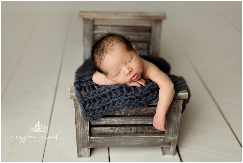 newborn baby boy on wooden bed in blue blanket online newborn workshop model