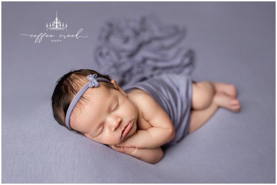 newborn baby girl asleep in purple