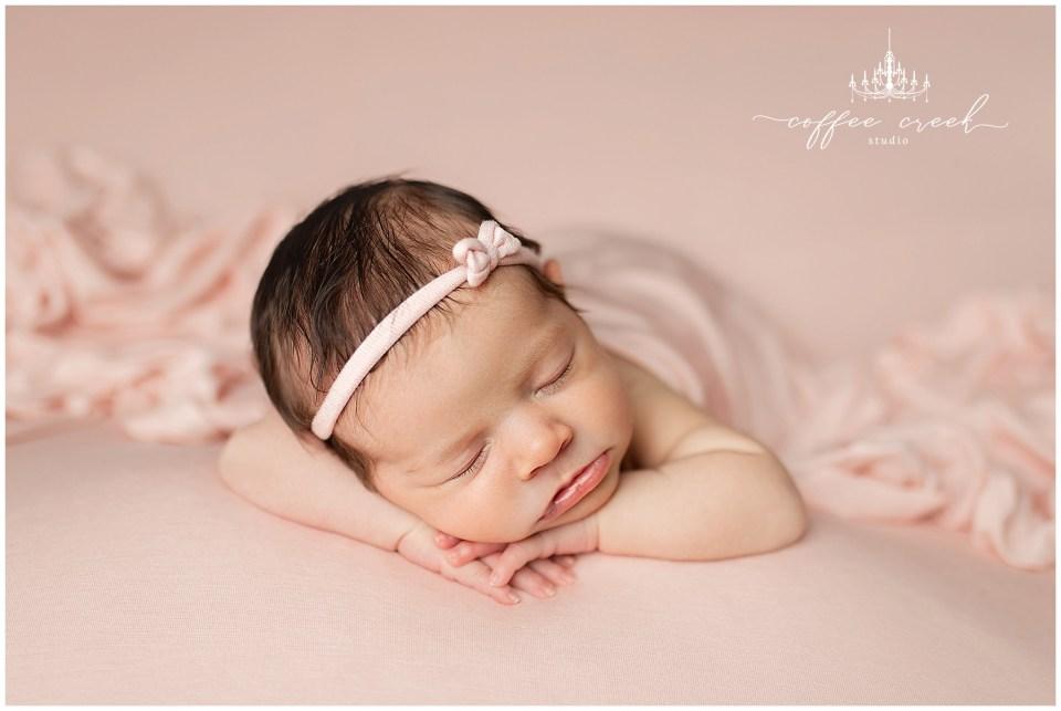 newborn baby girl head on hands in pink