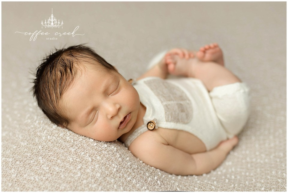 newborn baby on white in overalls