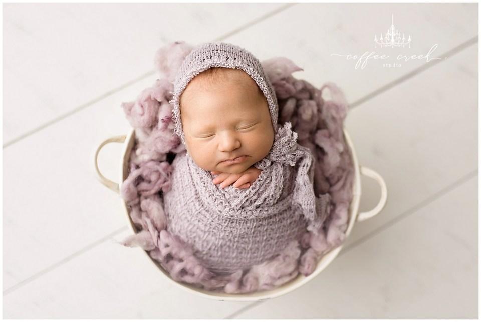 newborn baby girl in bucket in purple