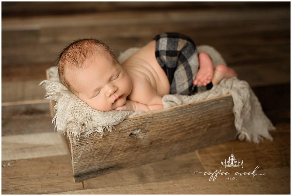 newborn baby boy posed on blanket in box