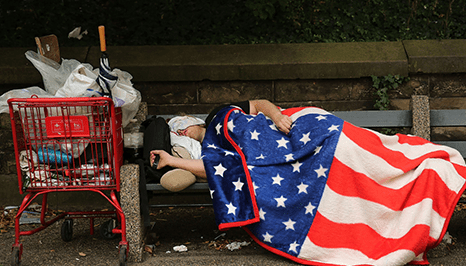 a closer look at the person on a park bench using a cloth as a blanket resembling the American flag