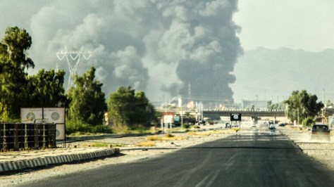 In this Thursday, July 31, 2014 photo, a column of smoke rises from an oil refinery in Beiji, some 250 kilometers (155 miles) north of Baghdad, Iraq, after an attack by Islamic militants.  AP Photo