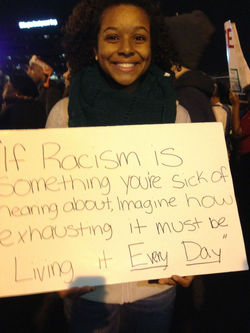 Young woman displays her sign which reads