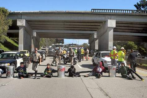 UC Santa Cruz students, chained together in concrete-filled trash cans, block Highway 1 at the entrance to Santa Cruz.