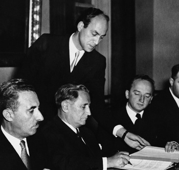 Nahum Goldman, the president of the Jewish Claims Commission (center), signs 1952 reparations agreements between Germany and Israel. The two delegations entered the room by different doors, and the ceremony was carried out in silence. (Associated Press)