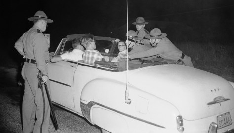 In August 1957, state police pull teenagers out of a car during a demonstration against Bill and Daisy Myers, the first African Americans to move into Levittown, Pennsyvlania. (AP Photo/Bill Ingraham)