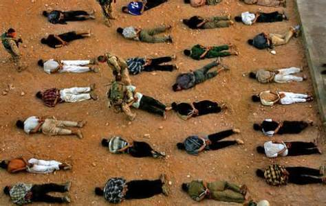 Iraq War, 2003-2010: Iraqi suspects have been detained by US forces and lie handcuffed face down on the ground. Photo by pinterest.com