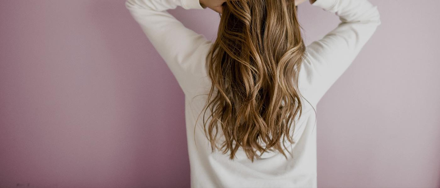 salon jolies momes coiffure orléans, cheveux bouclés et naturelles, femme de dos, mains dans les cheveux