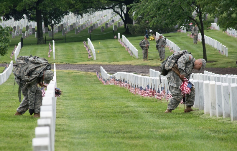 Members of The Old Guard place American flags at headstones at Arlington National Cemetery during Flags-In on May 21, 2015.