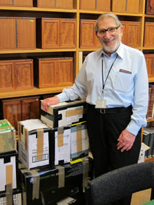 Professor Ted Buttrey with a cartload of numismatic sale catalogues in the Fitzwilliam Museum, Cambridge