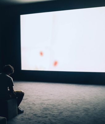 Una persona está en posición pensativa ante una gran pantalla que proyecta luz blanca.