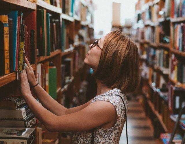 Una mujer busca entre las estanterías de una biblioteca.