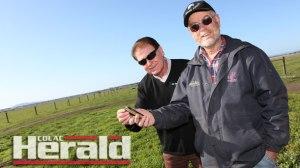 Barwon Water's agriculture water adviser Tom Macdonald and Irrewarra farmer Bill Dullard monitoring water loss on a mobile phone.