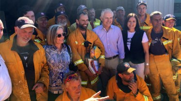 Prime Minister Malcolm Turnbull, centre third from right, his wife Lucy, second from left, and Corangamite MP Sarah Henderson, second from right, have praised members of the Wye River Country Fire Authority brigade for their role in saving more than 300 homes in Wye River and Separation Creek in the Otways' Christmas Day blaze. Mr Turnbull toured the scene of the bushfire yesterday.