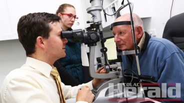 LUCKY: Phil Callahan, right, has avoided a stroke thanks to an eye test. Optometrist Leigh Plowman discovered an embolus in Mr Callahan's right eye. They are pictured with student optometrist Mary Knight.