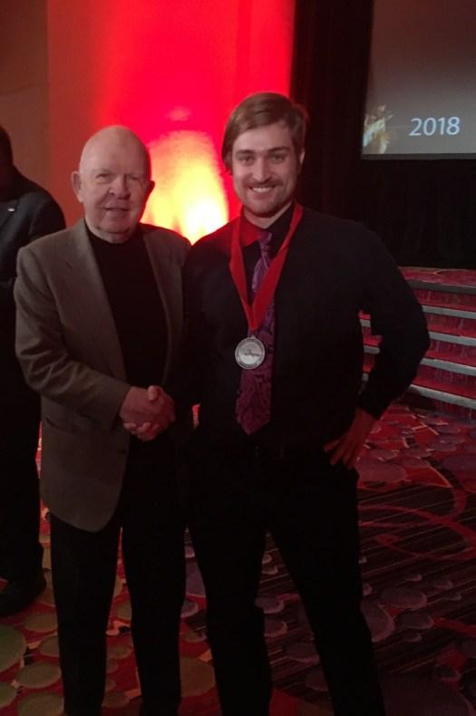 Colburn wearing award medallion shaking hands with John Rouche
